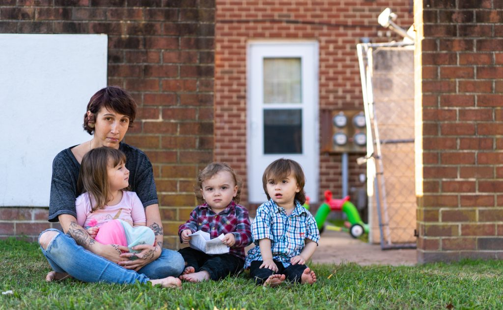 Kandise Norris, shown here with her three children in a Nov. 7 photo outside their home in Somerset County, Maryland, says she has been rebuilding her life since getting treatment for drug addiction in April 2019. The Housing Authority of Crisfield, which owns her house, has filed three eviction cases against the 30-year-old since September. (Nick McMillan/Howard Center)