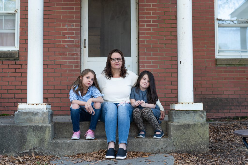 Margaret Szabo, 42, sits with her two daughters on the porch of their home in Richmond, Virginia, on Nov. 6. The Richmond Redevelopment and Housing Authority, which owns Szabo's home, filed an eviction case against her for unpaid rent last fall. She said an aid organization paid the back rent, but she's behind again in 2020. (Nick McMillan/Howard Center)